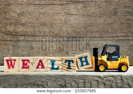 Yellow Toy Forklift Hold Letter Block H To Complete Word Wealth On Wood Background