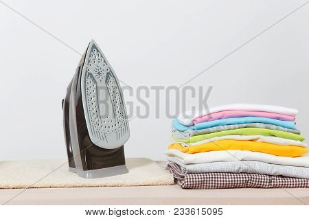 Close Up Steam Iron, Ironing Colorful Clothes, Washed Laundry, Family Clothing On Ironing Board Isol