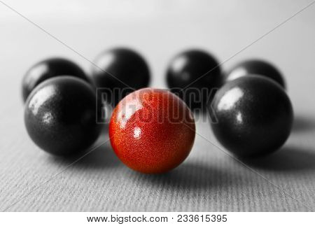 One brown ball among black ones on table. Difference and uniqueness concept