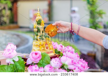 Bangkok, Thailand - April 13, 2017 :  Hand Pouring Water To Emerald Buddha With Pink Lotus On Songkr