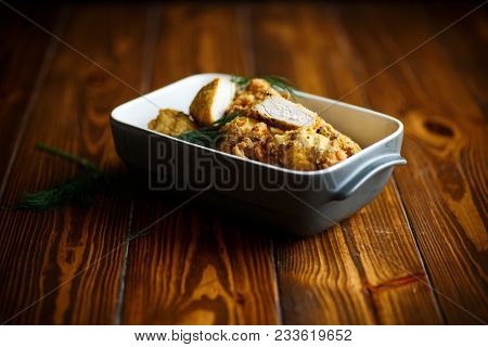 Chicken Fried In Batter With Dill In Ceramic Form On A Wooden Table