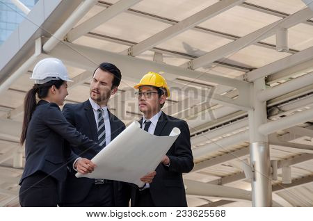Group Of Business Or Engineer Woman And Man With Safety Helmet, Blueprint Planning About New Project