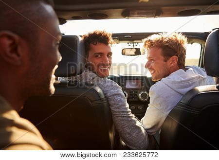 Three young adult men driving with sunroof open, back view