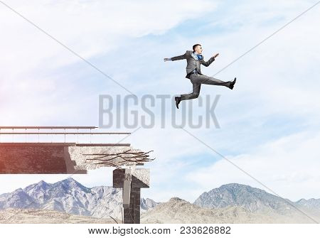 Businessman Jumping Over Huge Gap In Concrete Bridge As Symbol Of Overcoming Challenges. Skyscape An