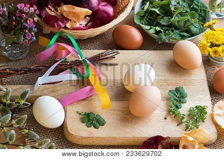 Preparation Of Easter Eggs For Dying With Onion Peels: Eggs, Onion Peels, And Fresh Green Leaves On