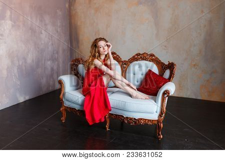 Luxurious Redhead Woman In A Red Dress On White Classic Couch In Minimalistic Loft Interior.