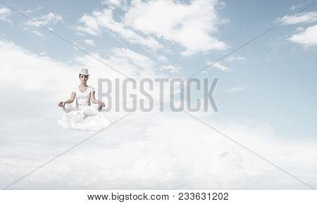 Woman In White Clothing Keeping Eyes Closed And Looking Concentrated While Meditating On Clouds In T