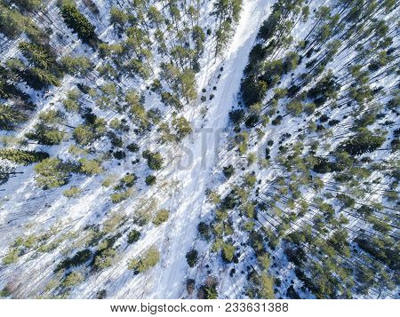 Aerial Drone View Of A Winter Road Landscape. Snow Covered Forest And Road From The Top. Sunrise In