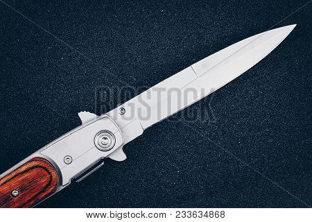 Folding Knife On Black Asphalt. Instrument Of Crime
