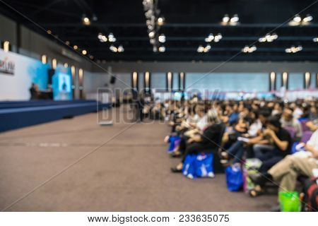Abstract Blurred Photo Of Conference Hall Or Seminar Room With Speakers On The Stage And Attende Bac