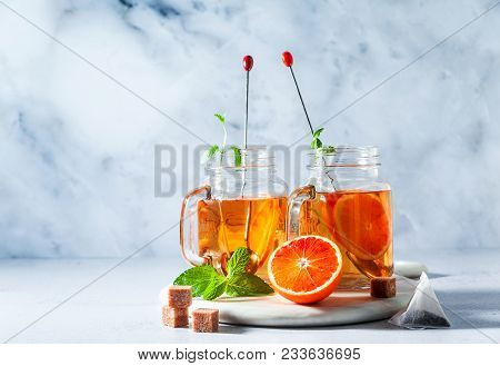 Traditional Iced Tea With Orange And Mint And Ice In Mason Jars . Refreshing Summer Drink On White M