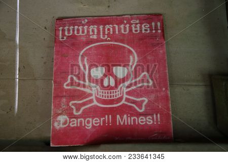 A Red Warning Sign With A Skull And Crossbones In Cambodia Intended To Warn People Of Landmines!