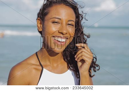Headshot of bright African-American woman with curly hair wearing white bikini and laughing at camera on shoreline of ocean.