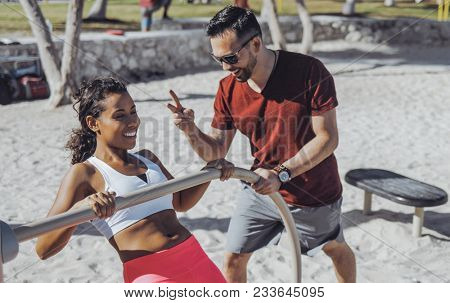 Cheerful man supporting young black woman while doing chin-ups on sandy beach with gym constructions.