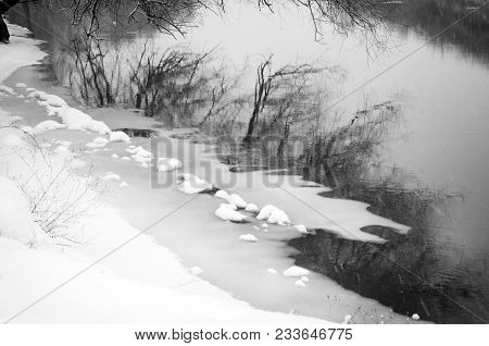Winter River. The Snow-covered Trees And The Shore Reflected In The Water