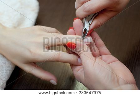 The Master Of The Manicure Cuts The Cuticles On The Hands In The Beauty Salon. Professional Hand Car