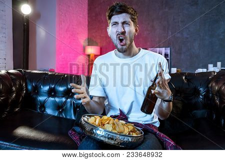 Young Man Watching Football Game On Television, Celebrating Goal, Crazy Happy Jumping On Couch At Ho
