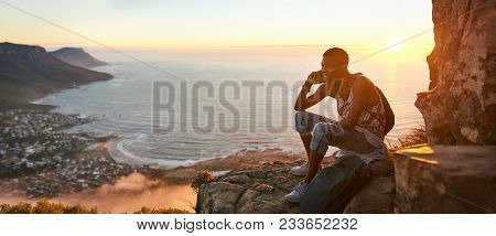 Panoramic Image Of A Young Black Man Sitting On The Top Of A Mountain Talking On A Mobile Phone Duri