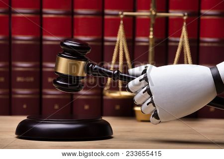 Close-up Of A Robotic Hand Striking Gavel On Sounding Block In Courtroom