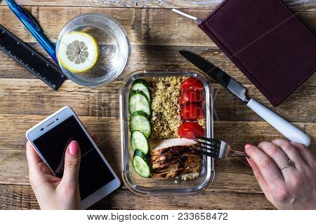 Hands Working On Mobile Cell Phone. Healthy Meal Prep Containers With Quinoa, Chicken And Arugula Se