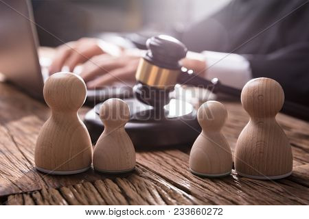 Separation Of Wooden Pawn Figure With Gavel In Courtroom