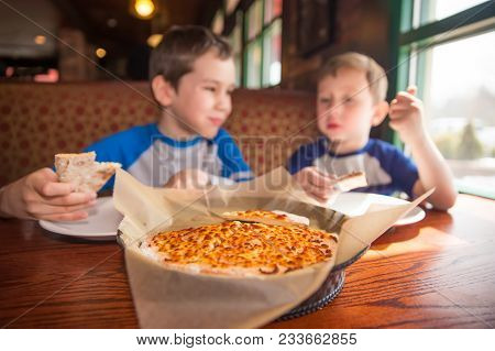 Kids Eating Pizza At Cafe. Children Eat Unhealthy Food Indoors. Selective Focus