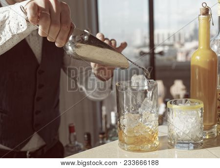 Barman is adding ice to mixing glass, making cocktail, toned image