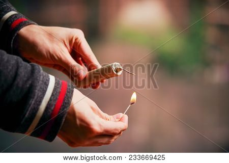 Close Up Of Man Hand Lighting Up A Firecrackers In A Burred Background.