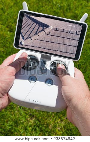 Hands Holding Drone Quadcopter Controller With Residential Roof Image on Screen.