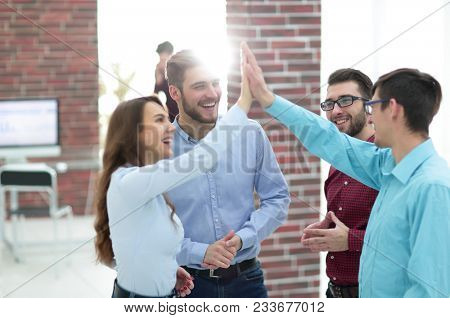 happy creative business people giving high-five in meeting room.