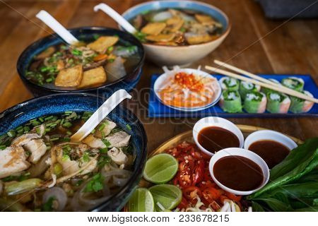 Traditional Vietnamese Food. Soups, Rolls And Fresh Herbs. Plates On A Wooden Surface. Healthy Veget