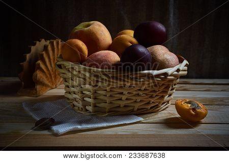 Fruit in a wicker basket on a wooden background in a low-key lighting.