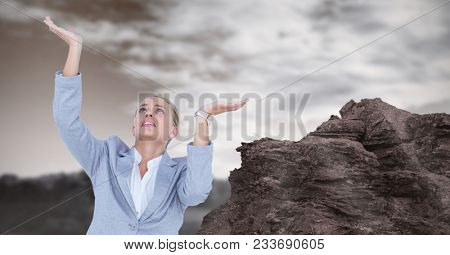 Digital composite of Businesswoman with arms raised by rock