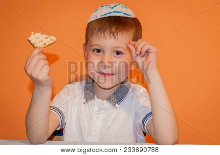 Happy Little Jewish Child With A Kippah On His Head And A Piece Of Matzo Bread In His Hands Looking