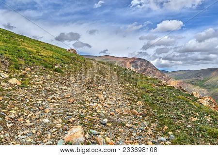 Rocky Dirt Steep Road Up Among The Stones High In The Mountains On The Background Of Blue Sky And Cl