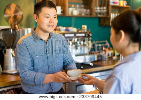 Happy Friendly Asian Man Giving Tasty Coffee To Customer. Cheerful Handsome Barista Brewing Coffee I