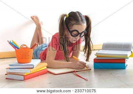 Homeschooling. The Child, The Pupil, The Schoolgirl Lies On A Floor With A Pile Of Books And Writes