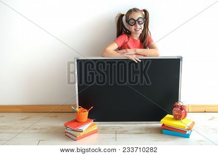 Homeschooling. The Child, The Pupil, The Schoolgirl With A Slate Board Against The Background Of A W