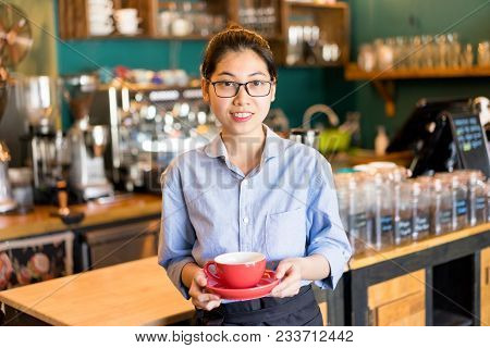 Friendly Asian Female Waitress Holding Coffee Cup And Looking At Camera. Cheerful Beautiful Young Ba