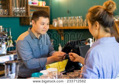 Friendly Cafe Cashier Accepting Payment From Customer And Taking Credit Card. Content Asian Coffee S
