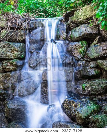 Cascading Small Water Fall In Green Nature