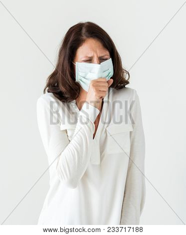 Sick woman wearing surgical mask coughing