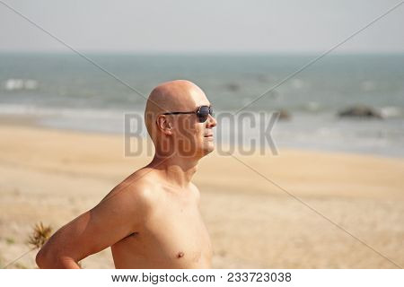 Bald Man With A Bare Bare Chest, In Striped Swimming Trunks Or Shorts Against The Background Of The
