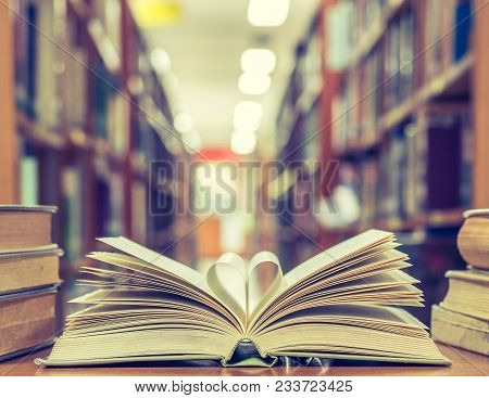 Love Story Book With Open Page Of Literature In Heart Shape And Stack Piles Of Textbooks On Reading