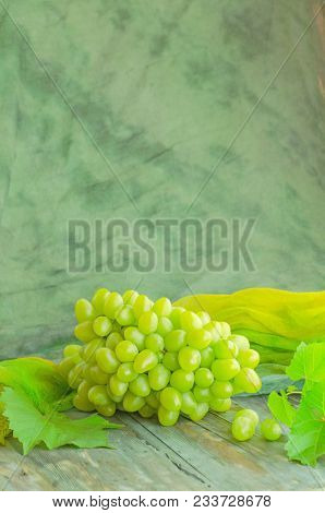 Green Grape On Wooden Background. Grapes With Leaves On The Board