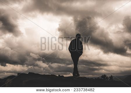 Boy Silhouette On The Background Of Clouds And Darkness. A Sense Of Loneliness, Freedom, Despair Or