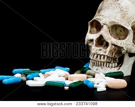 Human Skull On Multicolored Of Drug And Capsule Is On The Black Background. Close Up. We Are Against