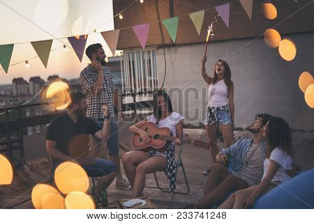 Young friends having fun at a summertime rooftop party, playing the guitar, singing, dancing and chilling out. Focus on the people in the middle poster