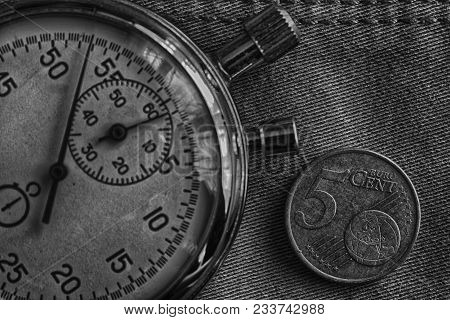 Euro Coin With A Denomination Of Five Euro Cents And Stopwatch On Worn Denim Backdrop - Business Bac