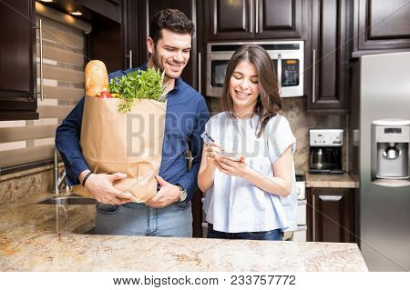 Happy Young Latin Couple In Kitchen Holding Grocery Shopping Bag And Looking At Small Diary List To